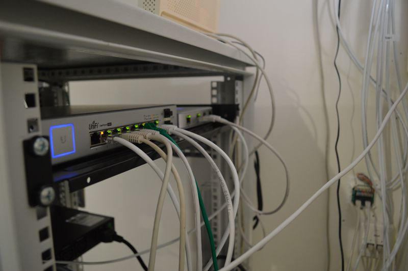 Unifi switch and router placed on shelf in rack